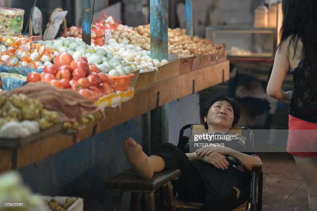 A vendor takes a rest in a wet market in Shanghai on July 15, 2013. China's gross domestic product expanded 7.5 percent in the April-June quarter, official data showed, a second consecutive slowdown in growth as worries mount over the health of the world's number two economy. AFP PHOTO/Peter PARKS