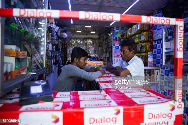 A vendor talks to a customer at a counter adorned with advertising for Dialog Axiata Plc in a mobile phone store in the Pettah neighborhood of...