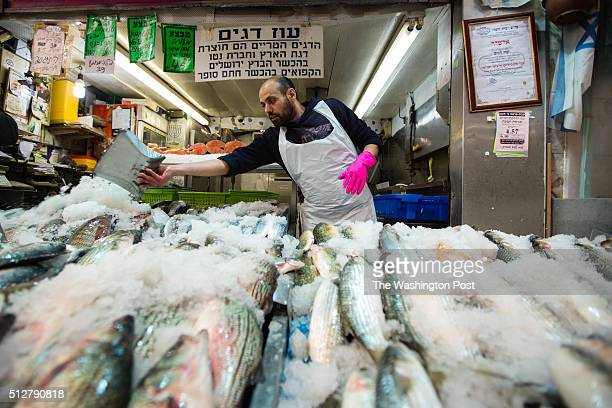 A vendor throws crushed ice over fish at the Mahane Yehuda Market often called 'The Shuk' on February 24 in Jerusalem Israel For a story by William...