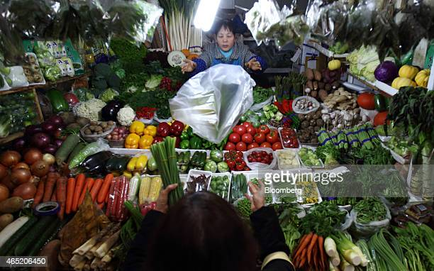 A vendor tosses a plastic bag to a customer at a vegetable stall in Beijing China on Wednesday March 4 2015 China's leaders are gathered this week in...