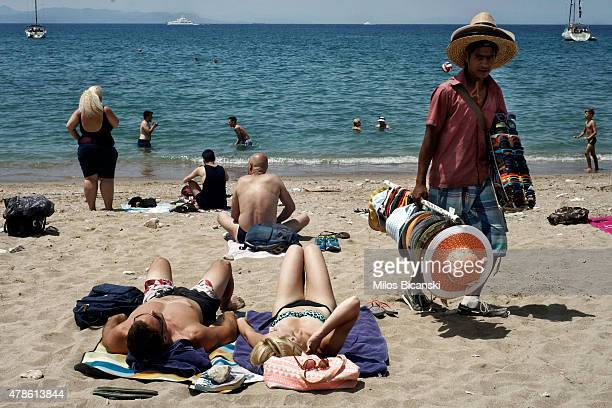 A vendor tries to sell his goods at a beach near Athens on June 26 2015 in Athens Greece This week the Greek goverment offered a series of measures...