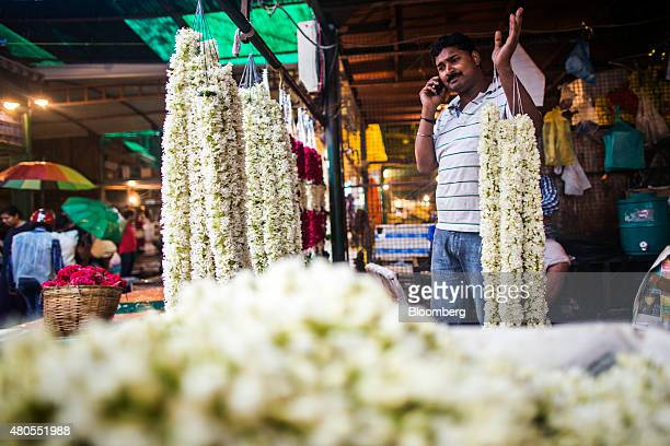 A vendor uses a mobile phone as he handles flower garlands at the Ghazipur Wholesale Flower Market in New Delhi India on Sunday July 12 2015 The top...