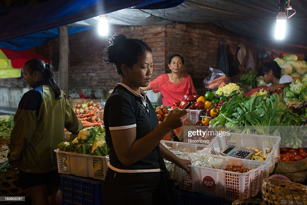 A vendor uses a mobile phone at a vegetable stall in the Pasar Badung market in Denpasar, Bali, Indonesia, on Tuesday, Oct. 8, 2013. Bank Indonesia said it will regulate currency hedging by individuals and companies, including state-owned firms, to help stabilize Asias most-volatile currency. Photographer: SeongJoon Cho/Bloomberg via Getty Images