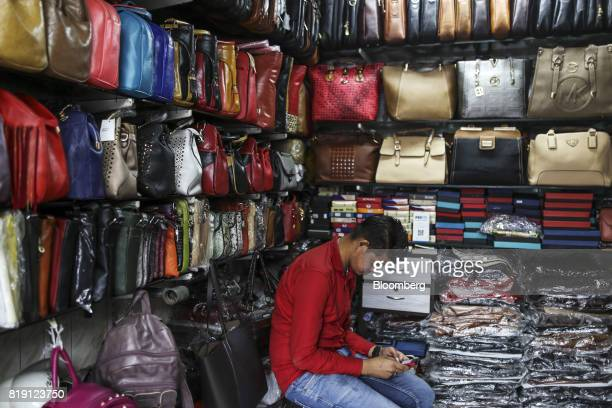 A vendor uses a mobile phone while waiting for customers at the Shakra Leather Arts store in the Dharavi area of Mumbai India on Tuesday July 18 2017...