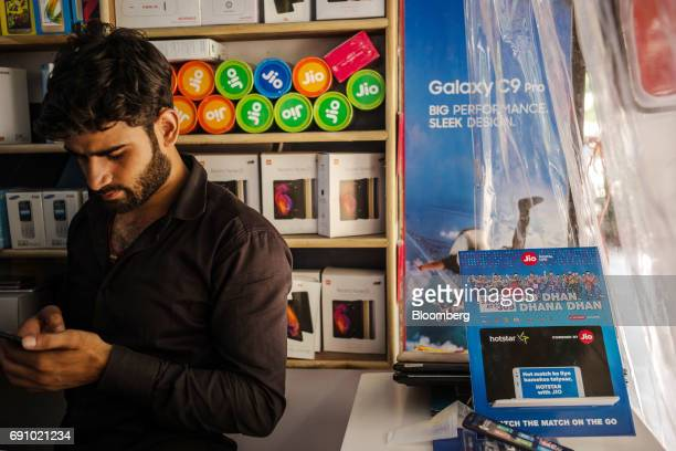 A vendor uses a smartphone while standing next to advertising for Reliance Jio Infocomm Ltd at the Nehru Place IT Market in New Delhi India on...