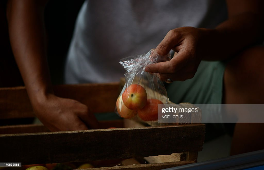 A vendor uses plastic to hold food at a wet market at Manila's financial district, Makati City, on June 20, 2013. The Philippines' financial centre banned disposable plastic shopping bags and styrofoam food containers on June 20, as part of escalating efforts across the nation's capital to curb rubbish that exacerbates deadly flooding. AFP PHOTO/NOEL CELIS