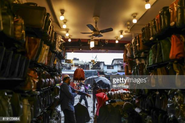 A vendor waits for a customers at a leather goods store in the Dharavi area of Mumbai India on Tuesday July 18 2017 India's new goods and services...