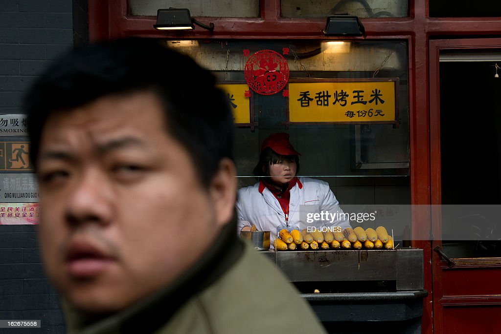 A vendor (R) waits for customers at her maize stall in Beijing on February 26, 2013. On March 5 China will convene a key legislative session, state media reported, with new Communist Party chief Xi Jingping set to become president during the two-week meeting. AFP PHOTO / Ed Jones