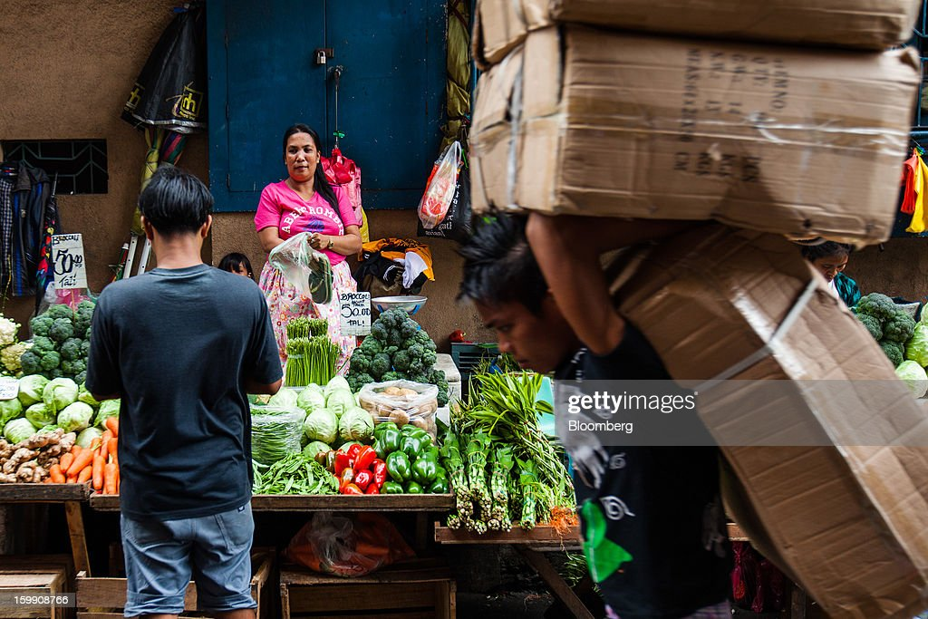 A vendor waits for customers at her vegetable stall as a laborer walks past carrying boxes of goods at the Divisoria market in Manila, the Philippines, on Tuesday, Jan. 22, 2013. Philippine government bonds advanced on speculation the central bank will hold its benchmark interest rate at a record low at a meeting tomorrow, supporting demand for the nation's debt. Photographer: Julian Abram Wainwright/Bloomberg via Getty Images