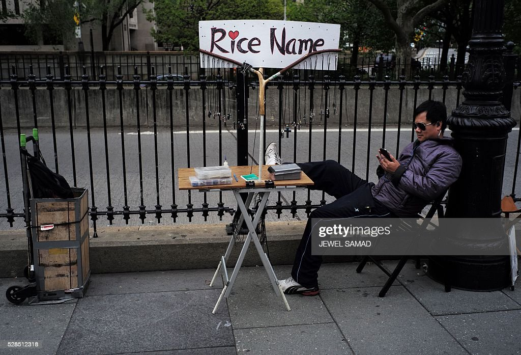 A vendor waits for customers displaying 'Rice Name' necklaces near the Brooklyn Bridge in New York on May 5, 2016. / AFP / Jewel SAMAD