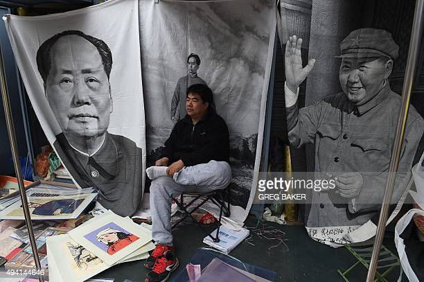 A vendor waits for customers for wall hangings of late communist leader Mao Zedong at a market in Beijing on October 25 2015 China's leaders will...