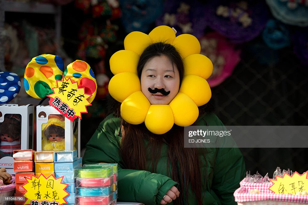 A vendor waits for customers in her stall at a temple fair in Ditan park in Beijing on February 9, 2013 a day before the Lunar New Year. China is preparing to welcome the lunar new year of the snake which falls on Febraury 10. AFP PHOTO / Ed Jones