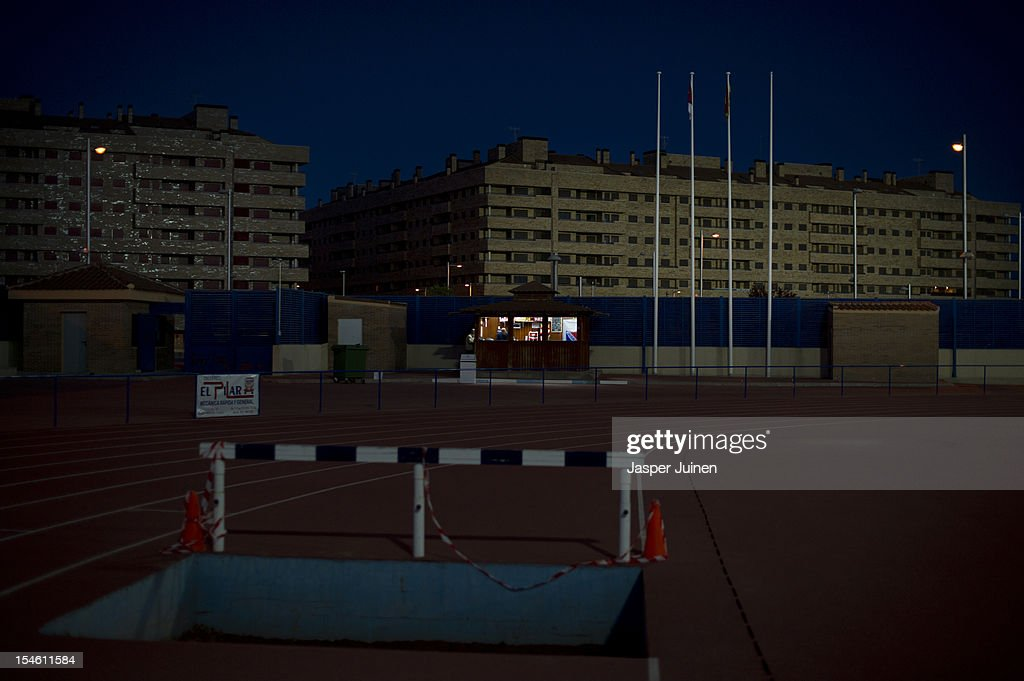 A vendor waits in an empty stall on a training ground backdropped by the many empty newly built apartment buildings on October 22, 2012 in Sesena, Spain. With a housing backlog of more than 1.2 million unsold newly build homes, banks in Spain have recenlty started to sell their real estate assets with discounts, some upto 80 percent, slashing prices to a level not seen for over 20 years. With morgages of 100 percent, some experts worry that mistakes from the past are repeated again.