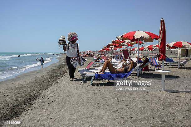 PETER FILES A vendor walks alongside sunbathers on the sands of Lido di Ostia Rome's nearest beach on July 17 2012 A law established in 2006...