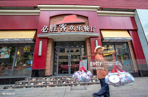 A vendor walks past a Pizzahut restaurant in Shenyang downtown According to the latest data revenue in China a critical market for Yum Brands fell 4...