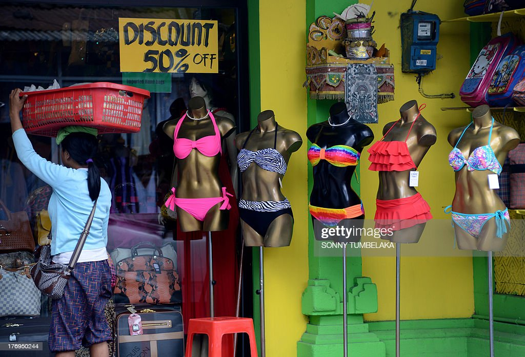 A vendor walks past bikinis on diaplay at a shop in Kuta on Bali island on August 20, 2013. Contestants at this year's Miss World beauty pageant will not wear bikinis in the parade in a bid to avoid causing offence in Muslim-majority Indonesia. The contest will be being held on the resort island of Bali. AFP PHOTO / SONNY TUMBELAKA