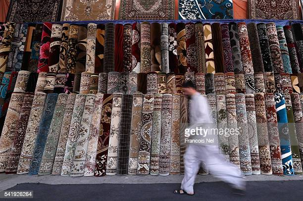 A vendor walks past carpets on display at the Friday market on June 21 2016 in Fujairah United Arab Emirates
