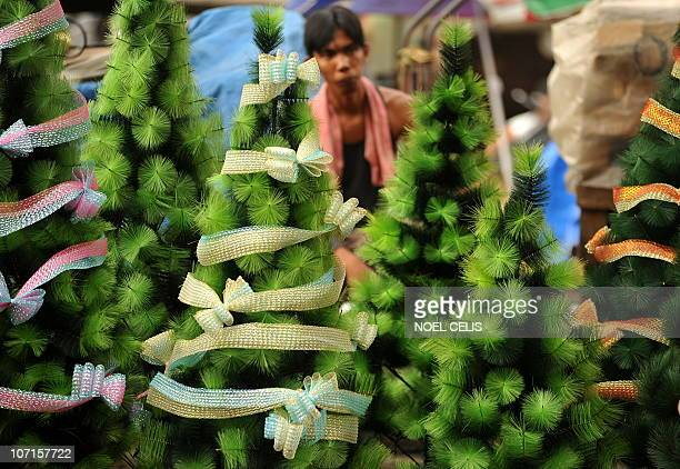 A vendor walks through christmas trees on sale at a stall in the Divisoria market in Manila on November 25 2010 Philippine economic growth slowed to...