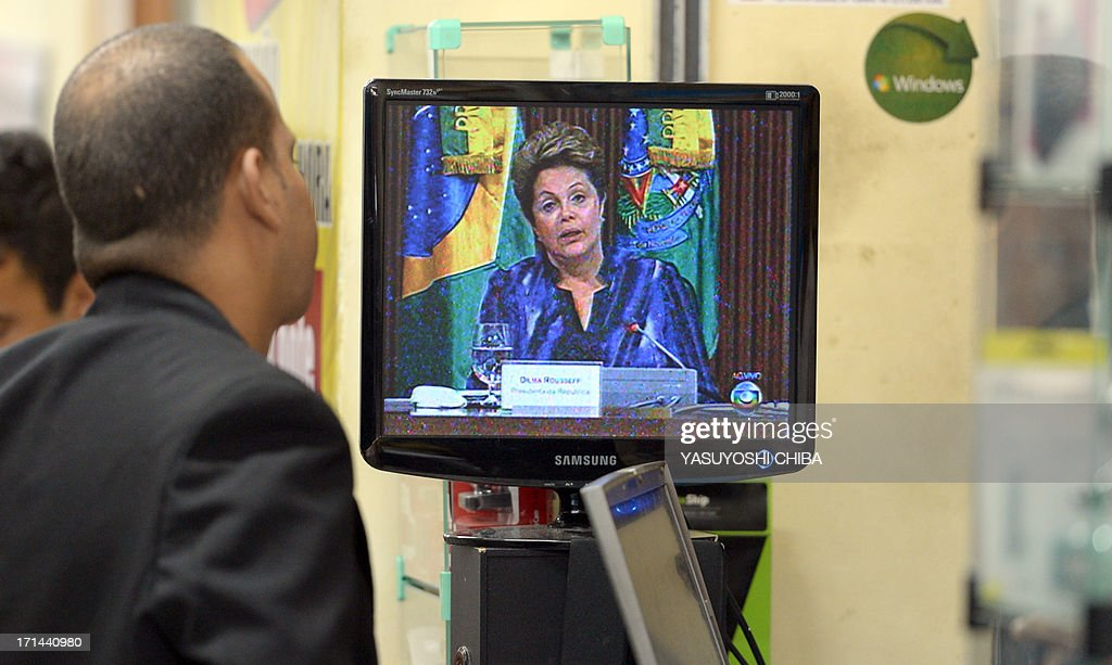 A vendor watches Brazilian president Dilma Roussef adress the nation and annouce spendings on the public transport system in a Rio de Janeiro shop on June 24, 2013. Brazil's President Dilma Rousseff tried to seize back control of the political initiative after weeks of mass street demos as Brazil hosts a dry run for the World Cup football, called the Confederations Cup.
