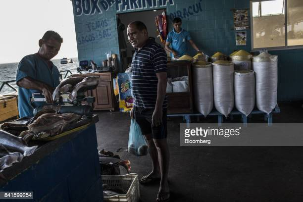 A vendor weighs fish for a customer at a market in Santarem Para State Brazil on Sunday Aug 20 2017 Brazil's economy unexpectedly grew in the second...