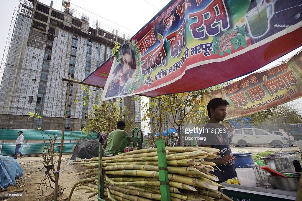 A vendor works at a sugarcane juice stall in front of a commercial building under construction in Gurgaon, India, on Wednesday, March 26, 2014. Indian stocks rose, sending the benchmark index to a record, after the rupee rose to an eight-month high and sovereign bonds gained on speculation the worlds largest democracy will elect a government capable of reviving economic growth. Photographer: Kuni Takahashi/Bloomberg via Getty Images