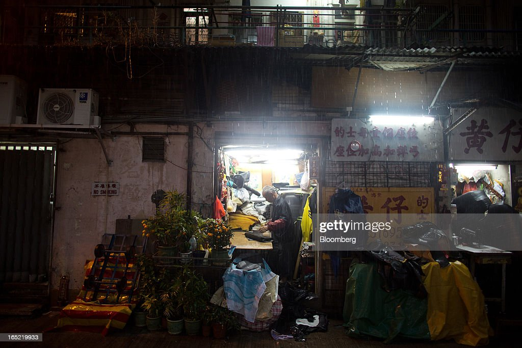 A vendor works inside an automotive upholstery workshop as rain falls at night in the Tai Hang area of Hong Kong, China, on Saturday, March 30, 2013. Rents are climbing in neighborhoods near Causeway Bay and Hong Kong's other prime shopping districts, known for luxury stores that attract free-spending tourists from mainland China. That's squeezing out mom-and-pop shops, congee and noodle vendors as developers and landlords seek to profit from the trend. Photographer: Lam Yik Fei/Bloomberg via Getty Images
