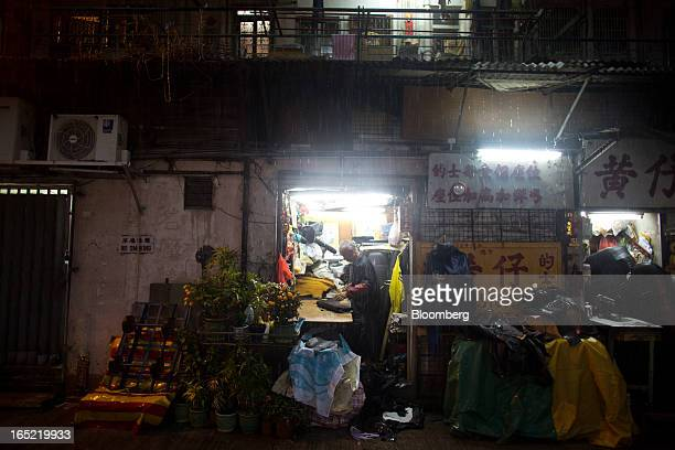 A vendor works inside an automotive upholstery workshop as rain falls at night in the Tai Hang area of Hong Kong China on Saturday March 30 2013...