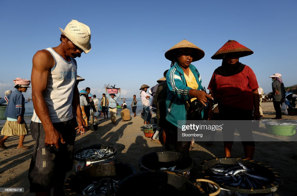 Vendors and fishermen stand next to crates of fish at Kedonganan beach in Jimbaran, Bali, Indonesia, on Saturday, Oct. 5, 2013. Indonesia's central bank kept its key interest rate unchanged after its most aggressive tightening cycle in almost eight years as inflation pressure eased. Photographer: SeongJoon Cho/Bloomberg via Getty Images