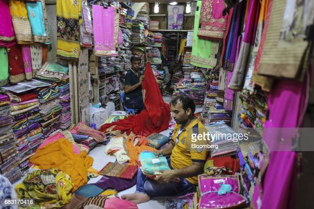 Vendors arrange saris at a wholesale store selling textiles inside Mangaldas Market in Mumbai India on Saturday May 13 2017 A Goods and Services Tax...