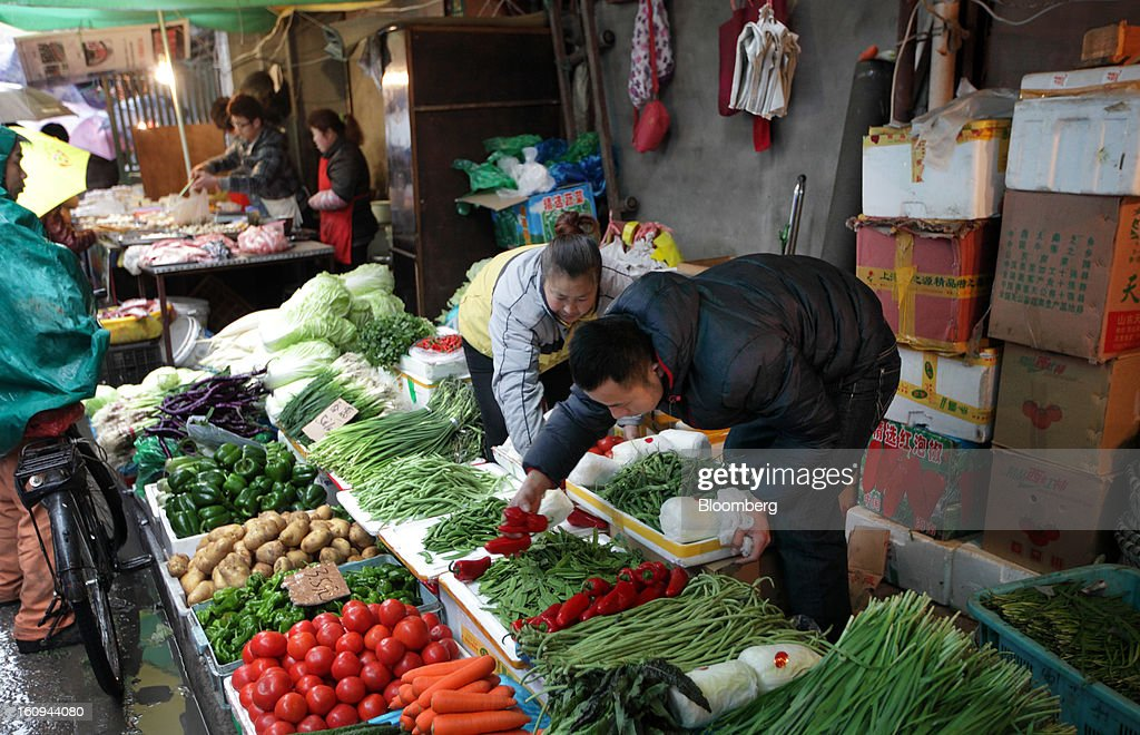 Vendors arrange vegetables at a market in Shanghai, China, on Thursday, Feb. 7, 2013. China's consumer prices rose 2 percent in January from a year earlier while the producer-price index dropped 1.6 percent, the National Bureau of Statistics said today in Beijing. Photographer: Tomohiro Ohsumi/Bloomberg via Getty Images