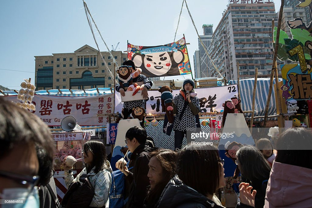 Vendors call for customers with a megaphone while holding stuffed toy monkeys at the Lunar New Year fair in Victoria Park in Hong Kong, China, on Sunday, Feb 7, 2016. The city's financial markets will close on Feb. 8 for the Lunar New Year holidays and resume trading on Feb. 11. Photographer: Billy H.C. Kwok/Bloomberg via Getty Images