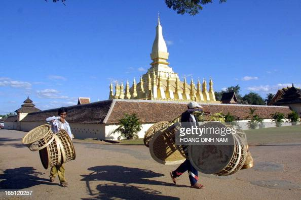 Vendors carry bamboo baskets walk past the That Luang tower in the centre of Vientiane on 25 November 2002 The buddhist country's symbol the tower is...