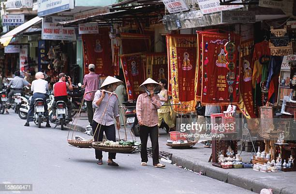 Vendors carrying traditional bamboo poles suspending baskets of their wares walk past shops in a street of old Hanoi north of Hoan Kiem Lake