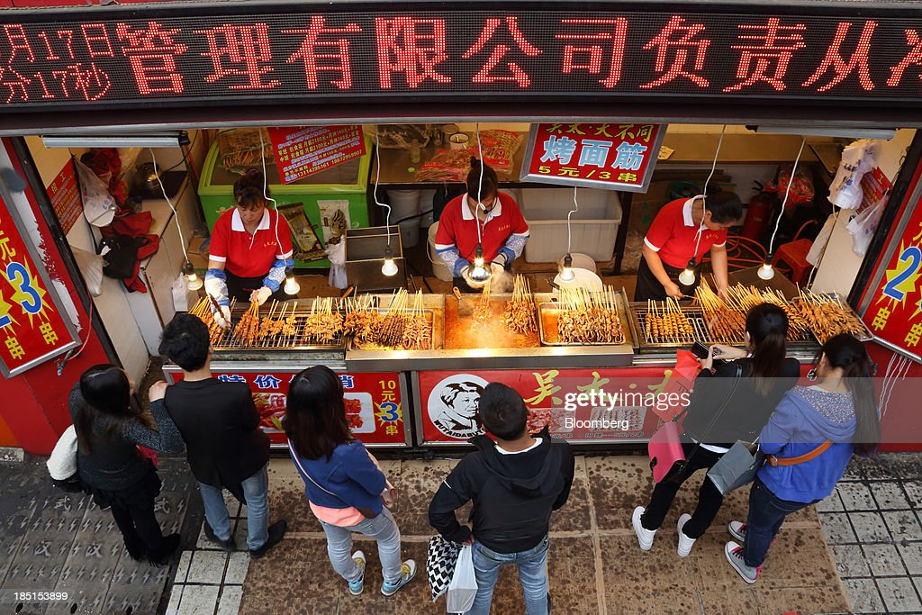 Vendors cook mutton skewers as customers wait at a stall in Wuhan, China, on Thursday, Oct. 17, 2013. China is scheduled to release third-quarter gross domestic product figures on Oct. 18. Photographer: Tomohiro Ohsumi/Bloomberg via Getty Images