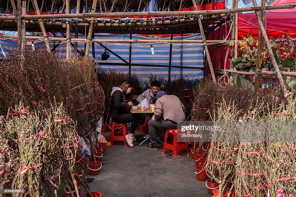 Vendors eat near peach blossom branches at a stall at a flower market in Victoria Park in Hong Kong, China, on Sunday, Feb 7, 2016. The city's financial markets will close on Feb. 8 for the Lunar New Year holidays and resume trading on Feb. 11. Photographer: Billy H.C. Kwok/Bloomberg via Getty Images
