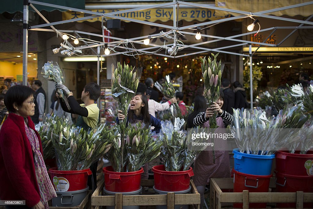 Vendors hold up lilies for sale for the Lunar New Year at a flower market in the Mongkok district of Hong Kong, China, on Wednesday, Jan. 29, 2014. The citys financial markets will close early on Jan. 30 for the Chinese New Year holidays and resume trading on Feb. 4, while those in the mainland will be shut from tomorrow through Feb. 6. Photographer: Brent Lewin/Bloomberg via Getty Images