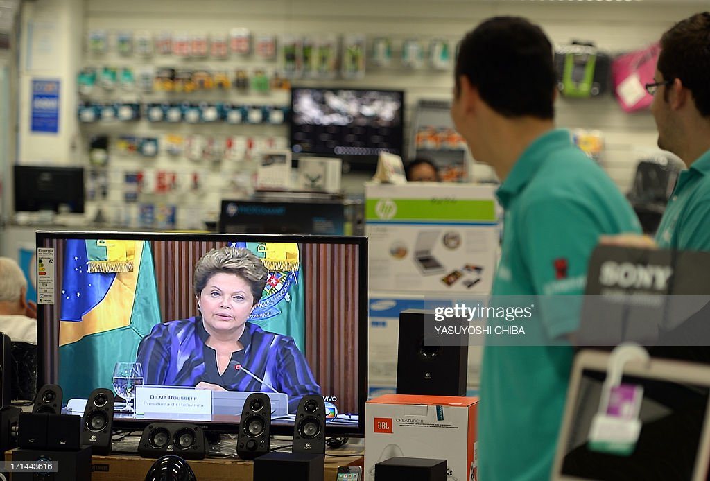 Vendors in a Rio de Janeiro shop watch Brazilian president Dilma Roussef adress the nation and annouce spendings on the public transport system on June 24, 2013. Brazil's President Dilma Rousseff tried to seize back control of the political initiative after weeks of mass street demos as Brazil hosts a dry run for the World Cup football, called the Confederations Cup.
