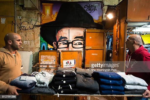 Vendors make preparations to close their stall as they pass in front of a graffiti depicting Rabbi Shlomo Ben David Lakein which was painted over a...