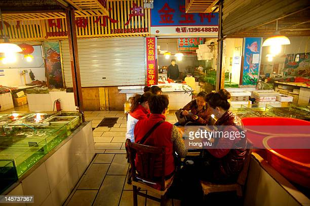 Vendors play card at a fish product market on May 23 2012 in Qingdao China Marine fishery resources in China becomes less and lees due to excessive...