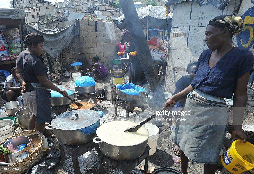 Vendors prepare food for sale on May 24, 2013, at an open-air market in the Petion-ville neighborhood of Port-au-Prince. AFP PHOTO/Thony BELIZAIRE