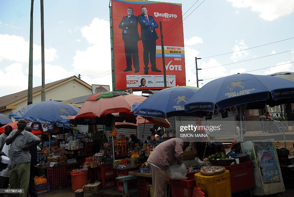 Vendors prepare their stands at an open air market next to a large billboard campaigning for presidential candidate Uhuru Kenyatta and his running-mate William Ruto on the outskirts of Nairobi, on February 27, 2013. Kenya is gearing up for presidential, gubernatorial, senatorial elections on March 4, the first since bloody post-poll violence five years ago in which more than 1,100 people died after contested results.