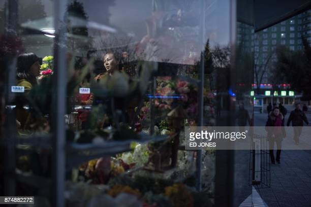 TOPSHOT Vendors prepares flowers for Mother's Day at a flower shop in Pyongyang on November 16 2017 North Koreans in Pyongyang typically mark...