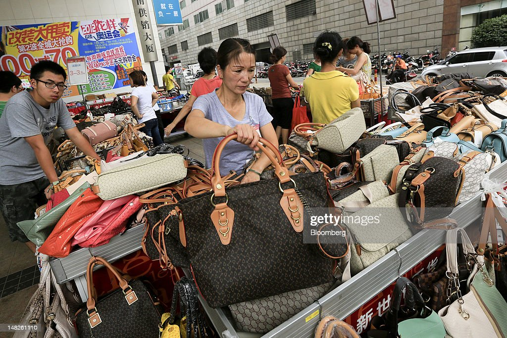 Vendors sell bags and purses outside a shopping mall in Changsha, Hunan Province, China, on Friday, July 13, 2012. Gross domestic product (GDP) expanded 7.6 percent in the second quarter of 2012 from a year earlier, China's National Bureau of Statistics said today in Beijing. Photographer: Nelson Ching/Bloomberg via Getty Images