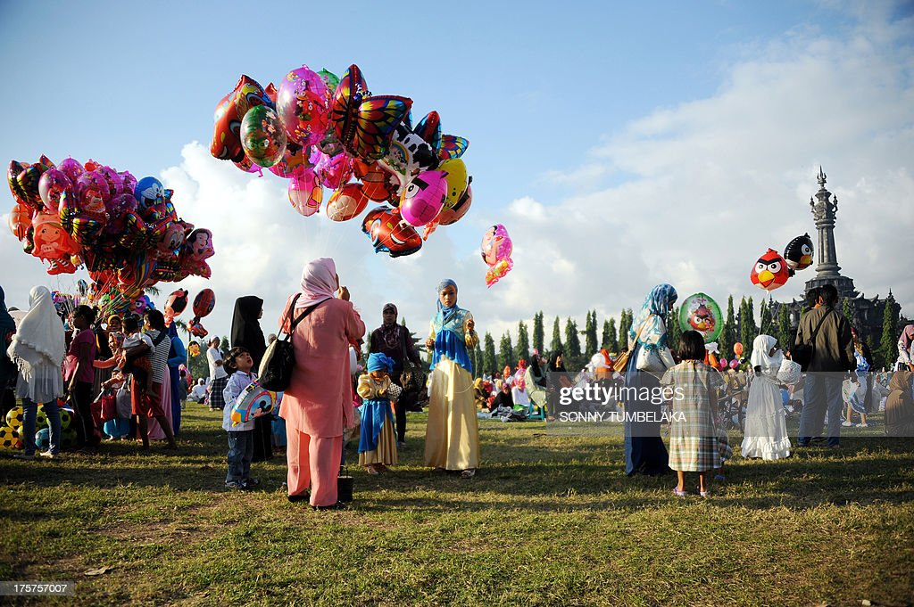 Vendors sell balloons for children as Indonesian Muslims gather to take part in special morning prayers near the Bajrah Sandhi monument in Denpasar on Indonesia's island of Bali on August 8, 2013. Muslims around the world will celebrate Eid al-Fitr this week, marking the end of holiest month of Ramadan during which followers are required to abstain from food, drink and sex from dawn to dusk. AFP PHOTO / SONNY TUMBELAKA