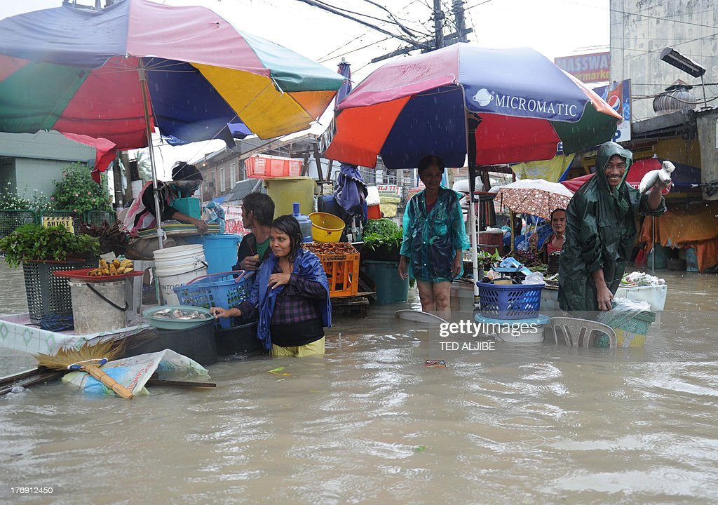 Vendors sell fish at a flooded market in Cavite, southwest of Manila on August 19, 2013. Torrential rain paralysed large parts of the Philippine capital August 19, as neck-deep water swept through homes, while floods in northern farming areas claimed at least one life.