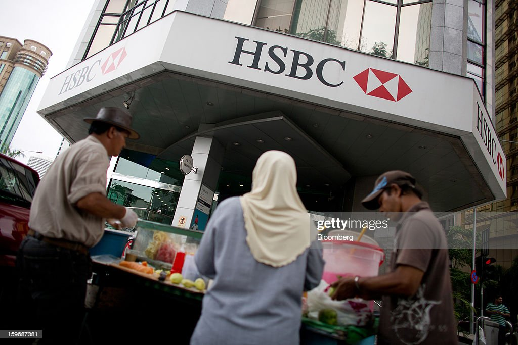 Vendors sell food outside an HSBC Holdings Plc bank branch in Kuala Lumpur, Malaysia, on Wednesday, Jan. 16, 2013. While many developed countries have faltered, Malaysia's gross domestic product growth has exceeded 5 percent for five quarters with domestic demand countering a slowdown in exports. Photographer: Lam Yik Fei/Bloomberg via Getty Images