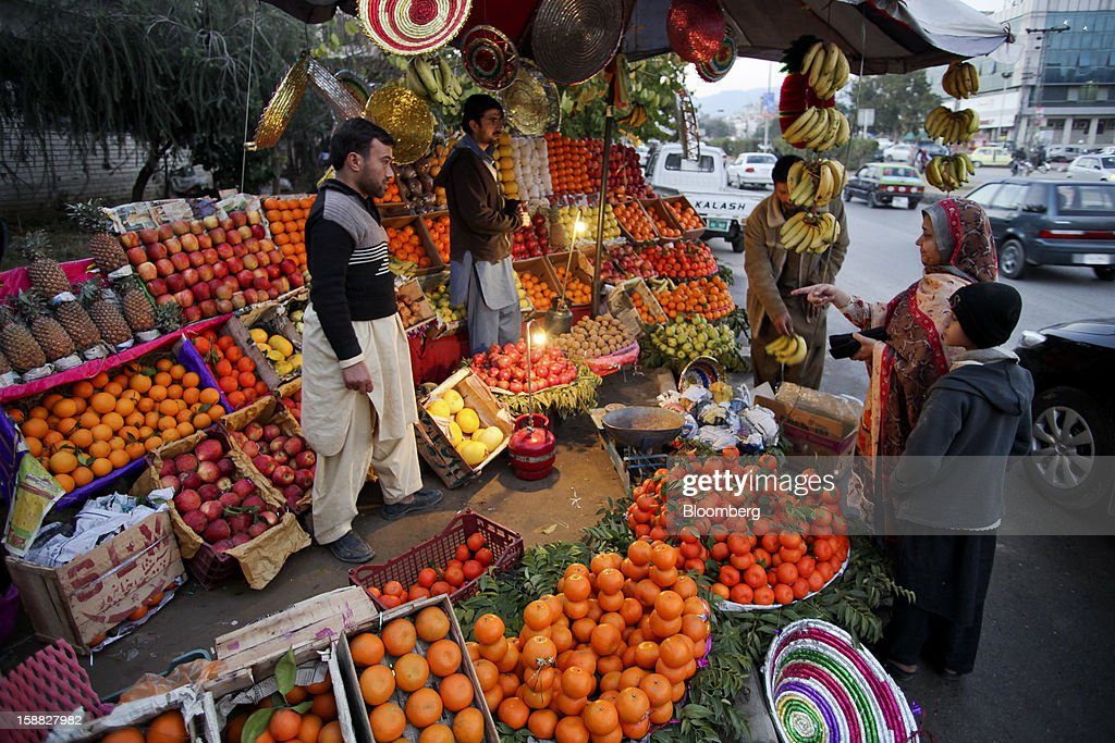 Vendors sell fruits by a road in Islamabad, Pakistan, on Sunday, Dec. 30, 2012. Pakistan's economy will probably expand 3.5 percent in the 12 months through June, the International Monetary Fund forecast Nov. 29, less than the 4.3 percent predicted by the government. Photographer: Asad Zaidi/Bloomberg via Getty Images
