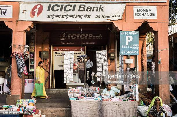 Vendors sell goods outside an ICICI Bank Ltd automated teller machine branch in Jaipur Rajasthan India on Wednesday Oct 3 2012 The Indian economy...