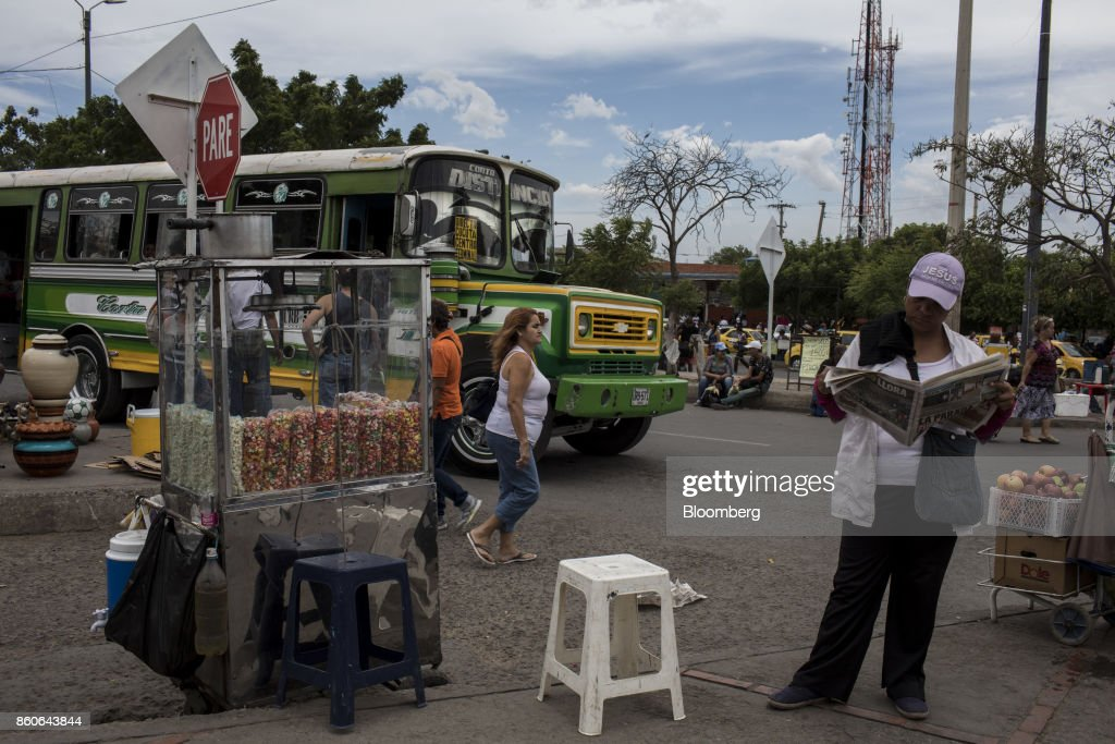 Vendors sell items next to a bus stop near the San Antonio International Border in Cucuta, Colombia, on Thursday, Sept. 21, 2017. For weeks, Venezuelans have been flocking by the busload to San Antonio del Tachira, a border town of some 62,000 residents, fleeing as President Nicolas Maduro consolidates autocratic power. According to Colombia's migration authority, the number of foreigners entering Cucuta, the first major city across the bridge, more than doubled this summer. Photographer: Nicolo Filippo Rosso/Bloomberg via Getty Images