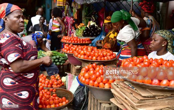 Vendors sell tomatoes at the large market of Adjame a popular district of Abidjan on August 10 2017 The Ivorian government in a council of ministers...